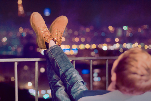 Girl gazing at the city lights in boke